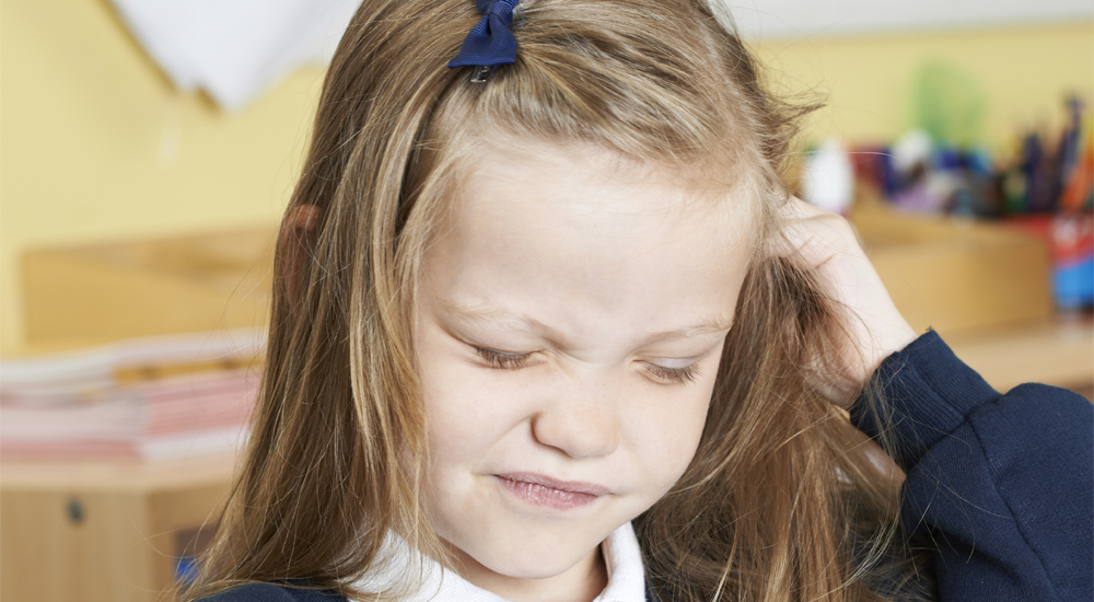 Fillette qui se gratte la tête à cause des poux en classe